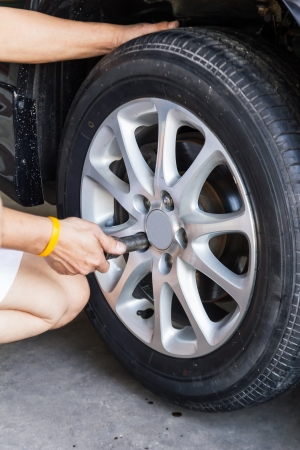 Replacing lug nuts by hand while changing tires on a vehicle  Stock Photo - 18275737