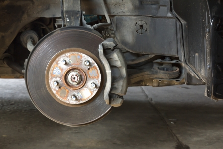 Front disk brake on car in process of damaged tyre replacement  The rim is removed showing the front rotor and caliper