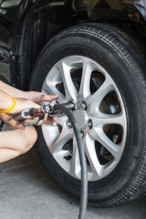 Replacing lug nuts by hand while changing tires on a vehicle Stock Photo - 18859702