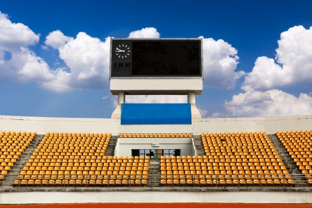 Rows of orange seats on the stadium with scoreboard displaying clock above them