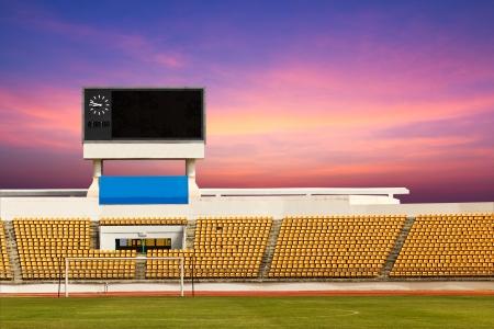 baseball stadium: Rows of orange seats on the stadium with scoreboard displaying clock above them