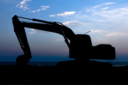 Excavator standing in sandpit with raised bucket at seaside Stock Photo