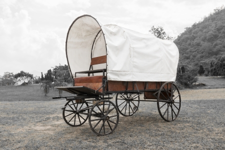 Old wagon wheels covered wagon  in park in black and white background photo