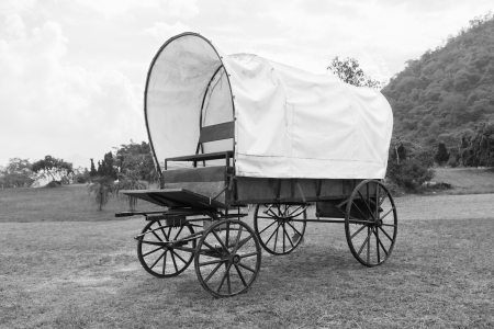 covered wagon: Black   White photo of old wagon wheels Covered wagon  in park