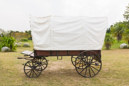 old wood farm wagon: Covered wagon with white top in park Stock Photo