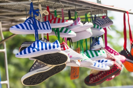 Lot of sneakers   shoes multicolored hanging on roof photo
