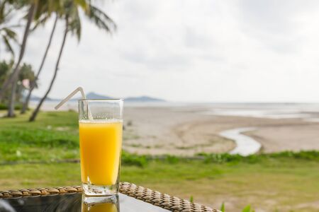 Glass of orange juice on table at tropical island beach photo