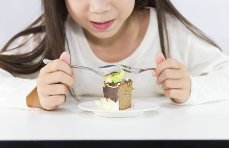 Girl eating cake   on white background photo