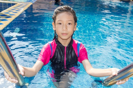 Girl relaxing on the side of a swimming pool photo
