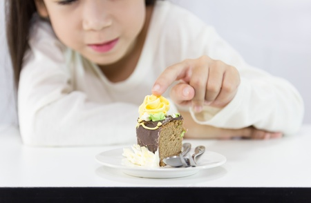 stared: The girl stared cake for overcome by a temptation to eat a slice of a sweet cake Stock Photo
