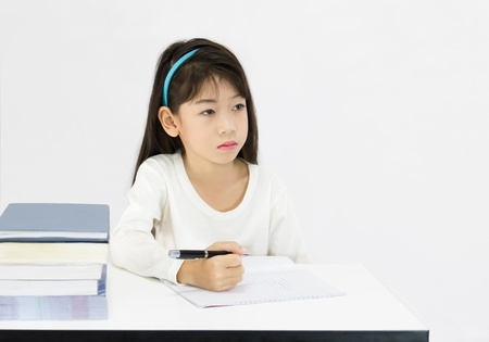Young girl working in classroom on white background