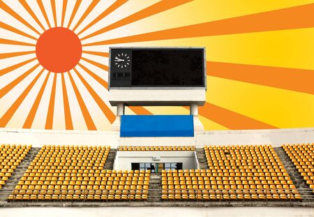 outdoor seating: Rows of orange seats on the stadium with scoreboard displaying clock above them and sun ray Stock Photo