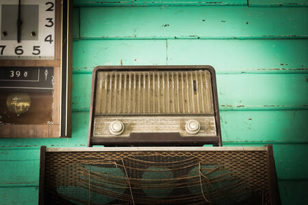 Retro Radio player and clock in room with green wood wall, photo