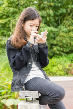 Beautiful Asian young girl using smartphone in park photo