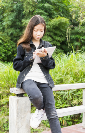 Beautiful Asian young girl using tablet computer in park photo