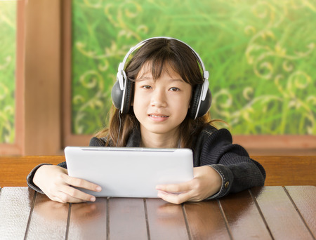 Portrait asian young girl is listening to music through headphones by sitting using Digital Tablet photo