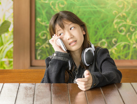 Asian young girl using mobile phone while sitting at desk photo