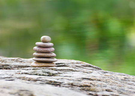 Stack of zen rocks in garden on green background photo