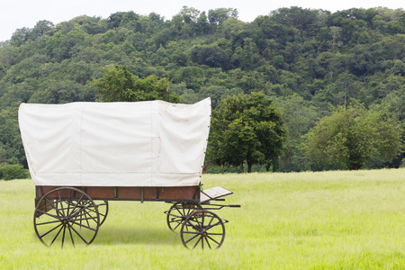 Covered wagon with white top in fields
