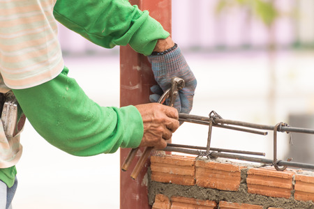 fixer: Workers using steel wire and pincers rebar before concrete is poured on brick wall