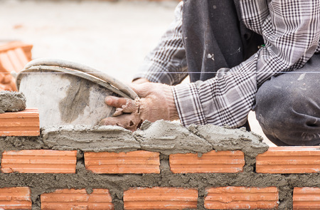 redbrick: Bricklayer working in construction site of a brick wall. Bricklayer putting down another row of bricks in site