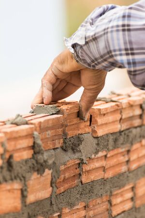 bricklayer: Bricklayer working in construction site of a brick wall. Bricklayer putting down another row of bricks in site