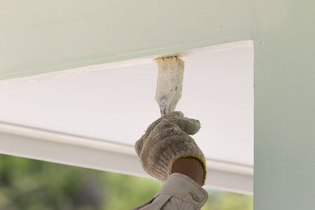 homeownership: Hand with paintbrush painting on the wall outdoor Stock Photo