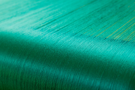 cloth manufacturing: Green silk on a warping loom of a textile mill, Silk for weaving on a hand loom Stock Photo
