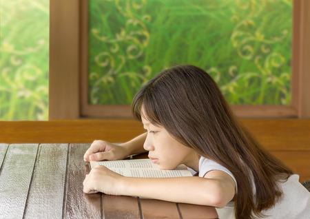 drowse: Asian girl bored learning while sitting at desk Stock Photo