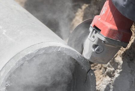 cutoff blade: Plumbers cutting concrete water pipes by metal grinding Stock Photo