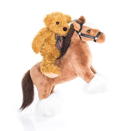 rustler: Teddy bear riding a horses on white background Stock Photo