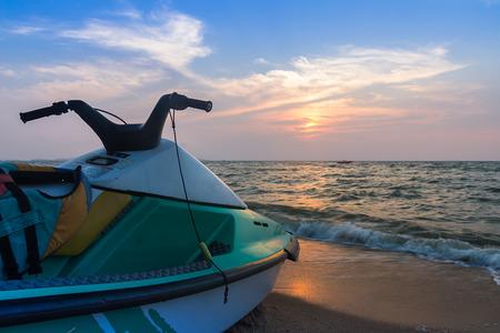 Jet ski on beach against blue sky and sunset