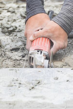 tile cutter: Mason cutting tiles to repair by metal grinding