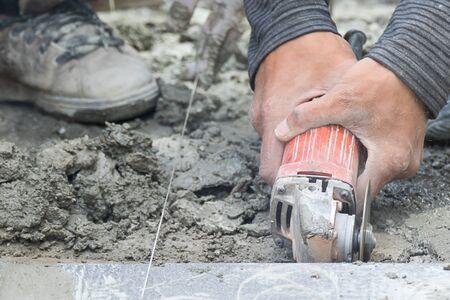 Mason cutting tiles to repair by metal grinding