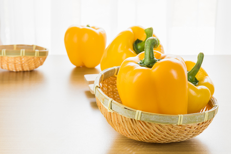 capsicum: Fresh yellow bell pepper (capsicum) in basket on wood table Stock Photo