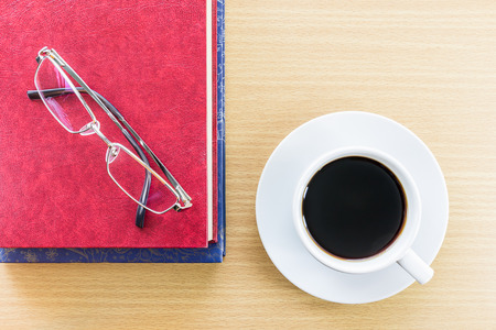 put on: Cup of coffee on wood table and glasses put on red book Stock Photo