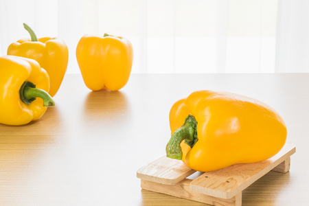 capsicum: Fresh yellow bell peppers (capsicum) on wood tray