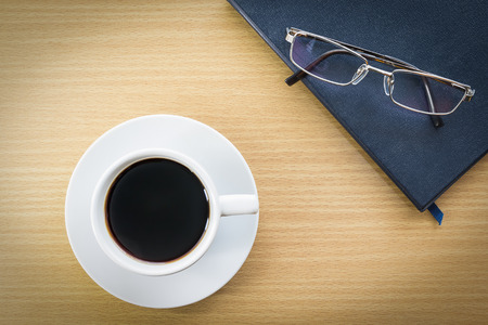 put on: Cup of coffee on wood deck and glasses put on book