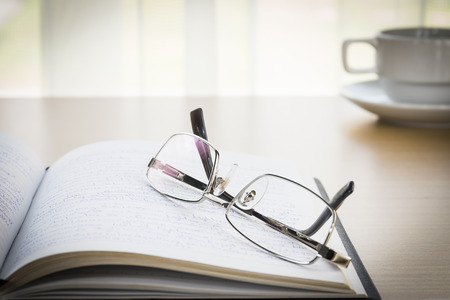 put on: Eyeglasses put on a book with on the desk,  Natural light from window