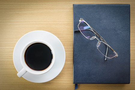 put on: Cup of coffee on wood table and glasses put on book