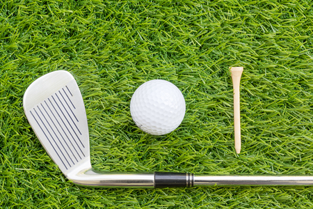 golfcourse: Sport objects related to golf equipment ,Golf club and golf ball on green grass