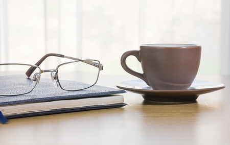 cofee: Glasses put on book and cofee cup on the desk by nature light from window