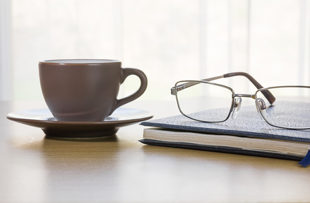cofee cup: Glasses put on book and cofee cup on the desk by nature light from window
