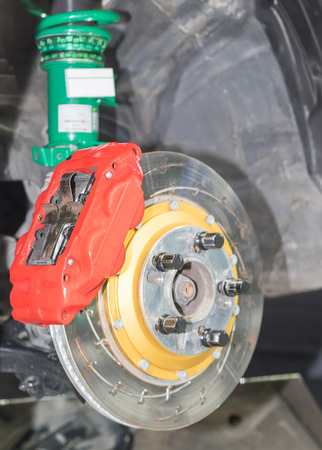 brake caliper: Front disk brake system on car in process of damaged tyre replacement. The rim is removed showing the front rotor and caliper.