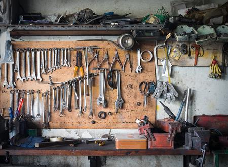 Oude hulpmiddelen die op muur in workshop hangen, Hulpmiddelplank tegen een muur Stockfoto - 59031834