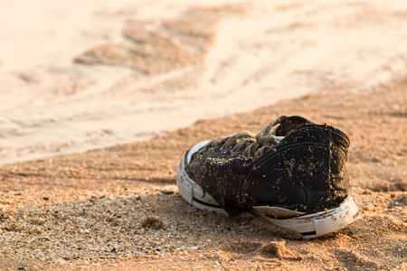 foot gear: Old black sneakers abandoned on the sand at the beach