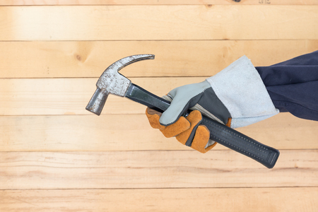 Working hand in glove holding a hammer with wall wood background Stock Photo