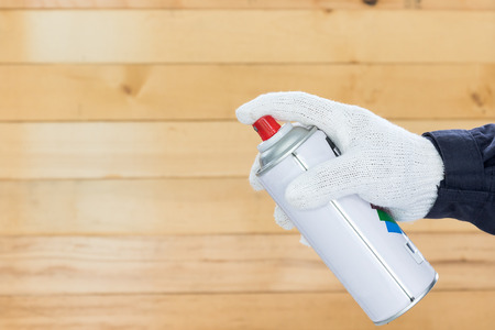 Working hand in glove holding spray paint can with wall wood background