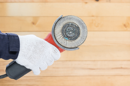Hand in glove holding Circular saw with an abrasive disk for wood grinding with wall wood background
