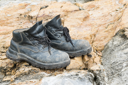 Closeup of trekking leather boot on the rock in mountain